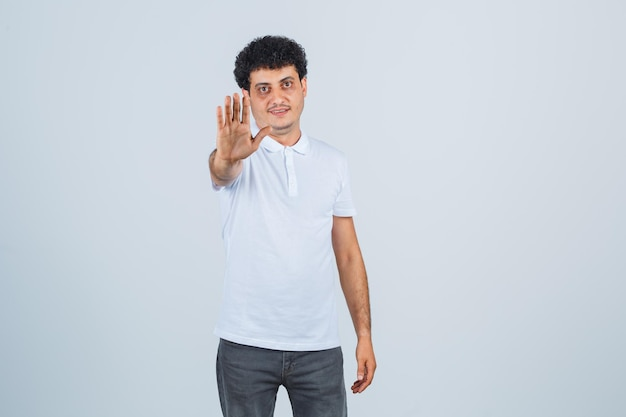Jovem macho em t-shirt branca, calças mostrando gesto de pare e parecendo confiante, vista frontal.