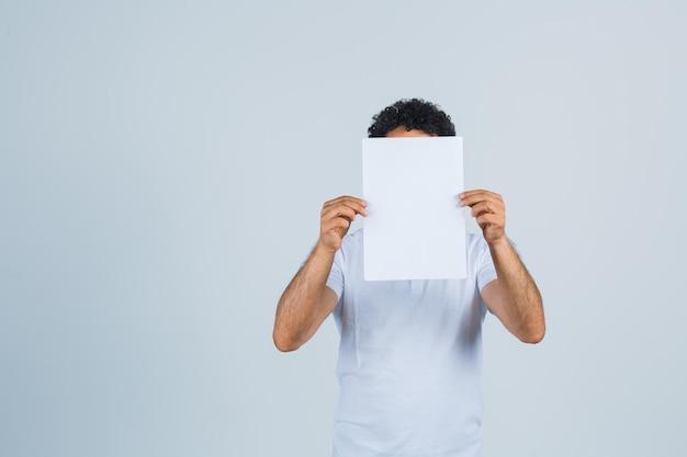 Jovem macho em t-shirt branca, mantendo a folha de papel em branco e parecendo confiante, vista frontal.