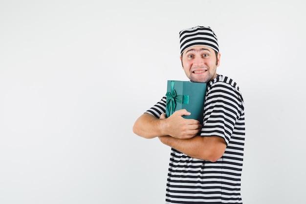 Jovem macho em t-shirt, chapéu, abraçando a caixa de presente e parecendo feliz, vista frontal.
