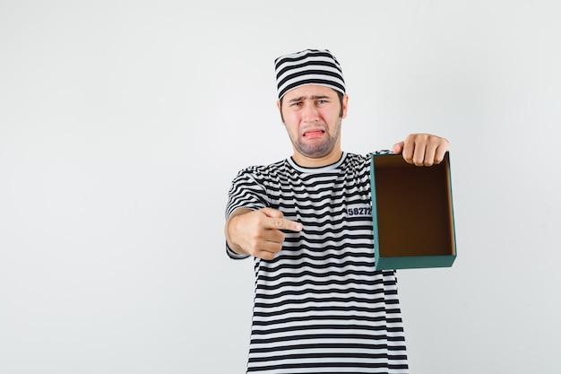 Jovem macho em t-shirt, chapéu, apontando para a caixa de presente vazia e olhando para baixo, vista frontal.