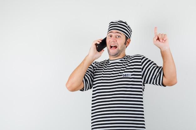 Jovem macho em t-shirt, chapéu, falando no celular, apontando para cima e parecendo feliz, vista frontal.