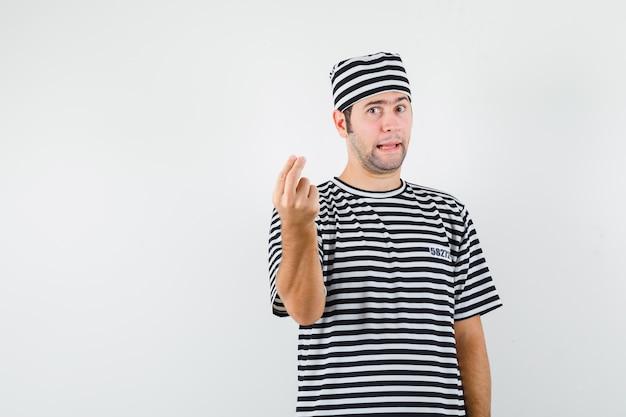 Jovem macho em t-shirt, chapéu, fazendo gesto italiano, ficar descontente com a pergunta idiota, vista frontal.