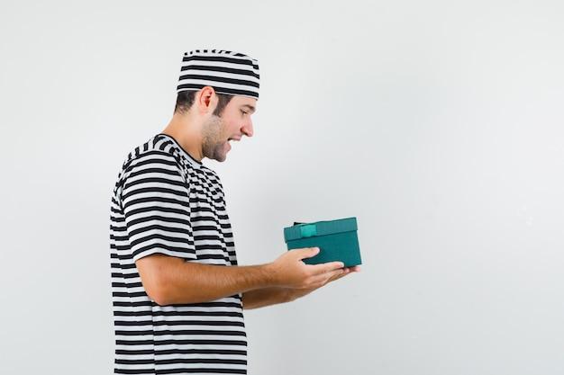 Jovem macho em t-shirt, chapéu, olhando para a caixa de presente e olhando focado.