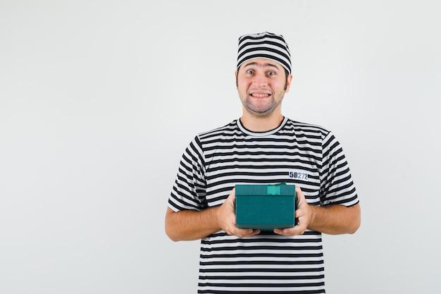 Jovem macho em t-shirt, chapéu segurando a caixa de presente e olhando alegre, vista frontal.