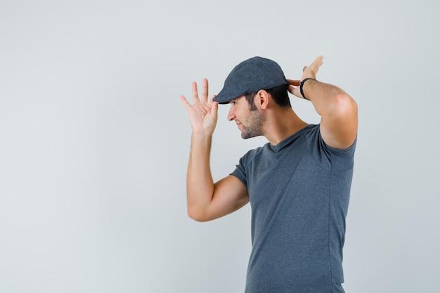 Jovem macho em t-shirt cinza usando boné e olhando confiante, vista frontal.