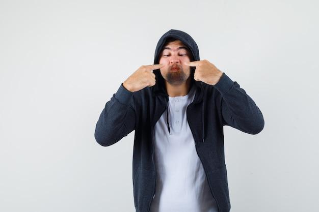 Jovem macho em t-shirt, jaqueta apontando para o nariz e olhando com foco, vista frontal.