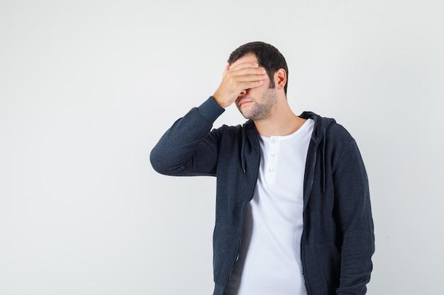 Jovem macho em t-shirt, jaqueta, segurando a mão no rosto e parecendo esquecido, vista frontal.