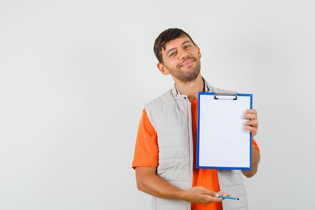Jovem macho em t-shirt, jaqueta segurando uma prancheta e lápis e olhando alegre, vista frontal.