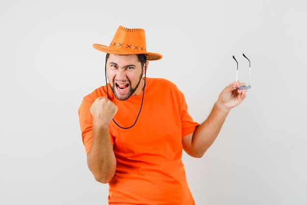 Jovem macho em t-shirt laranja, chapéu segurando óculos com gesto de vencedor e olhando feliz, vista frontal.