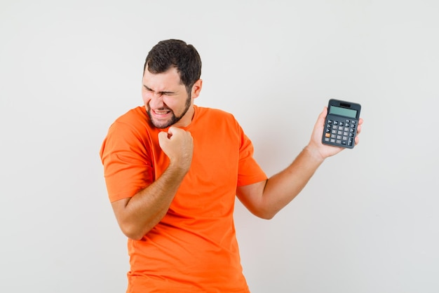 Jovem macho em t-shirt laranja segurando calculadora com gesto de vencedor e olhando feliz, vista frontal.