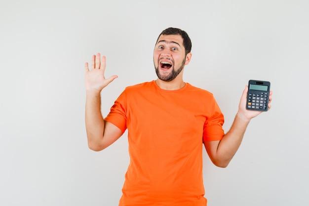 Jovem macho em t-shirt laranja segurando calculadora, mostrando a palma da mão e parecendo feliz, vista frontal.