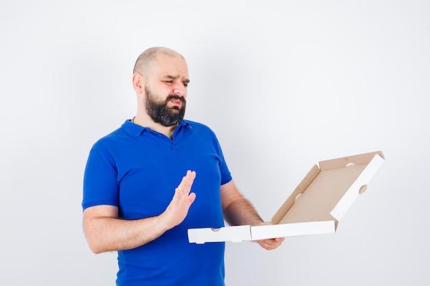 Jovem macho em t-shirt mostrando gesto de recusa e parecendo confuso, vista frontal.