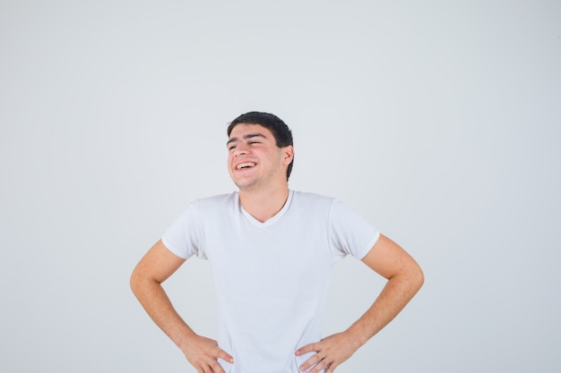 Jovem macho em t-shirt posando com as mãos na cintura e olhando alegre, vista frontal.