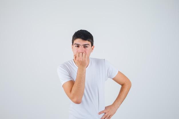 Jovem macho em t-shirt roendo as unhas e parecendo pensativo, vista frontal.