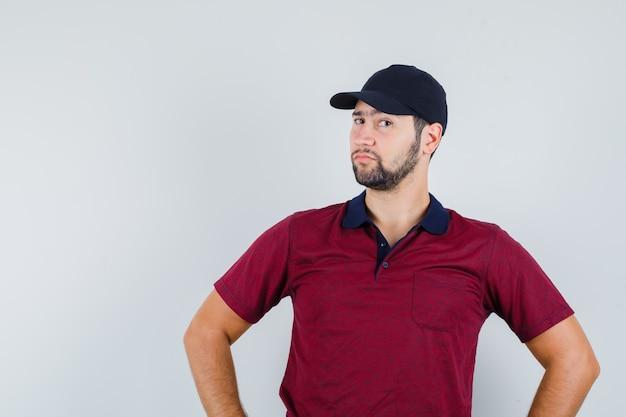 Jovem macho em t-shirt vermelha, boné preto em pé e parecendo estranho, vista frontal.