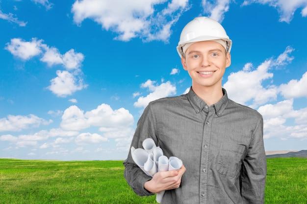 Jovem, macho, engenheiro, com, capacete, segurando, desenhos técnicos