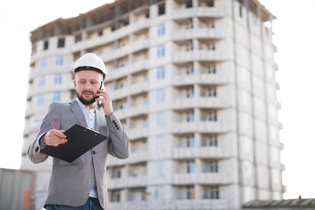 Jovem, macho, engenheiro, falando, ligado, cellphone, enquanto, segurando clipboard, em, local construção