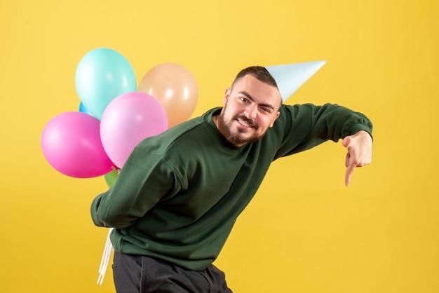 Jovem macho escondendo balões coloridos atrás das costas em fundo amarelo