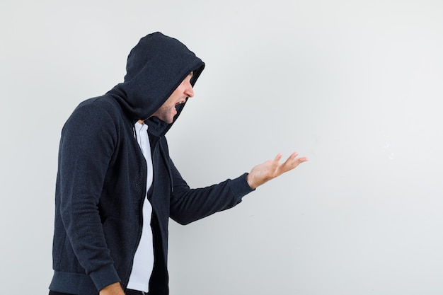 Jovem macho, esticando a mão em um gesto de questionamento em t-shirt, jaqueta e olhar zangado.