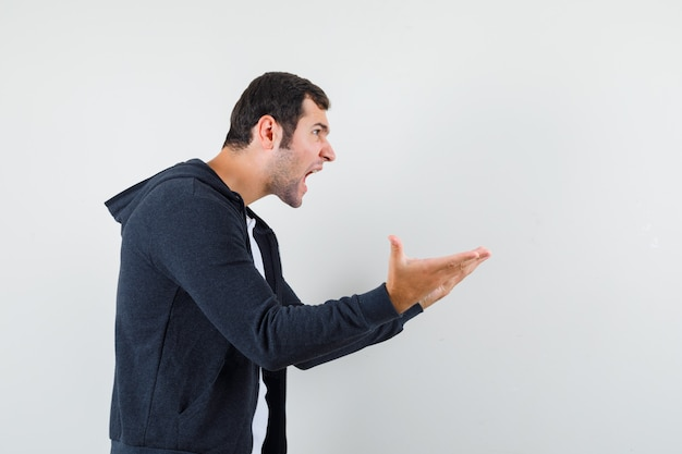 Jovem macho esticando as mãos em um gesto de questionamento em t-shirt, jaqueta e olhar zangado. .