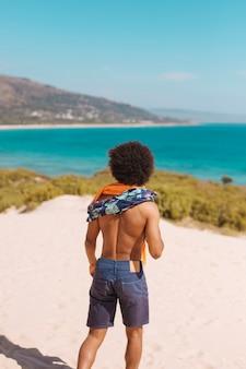 Jovem macho étnico admirando a beira-mar