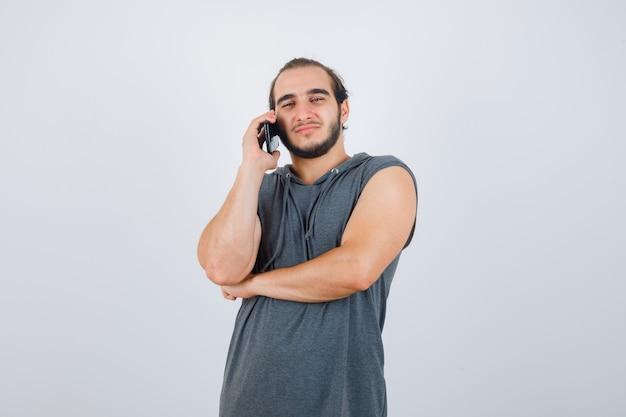 Jovem macho falando no celular com capuz sem mangas e está bonito. vista frontal.