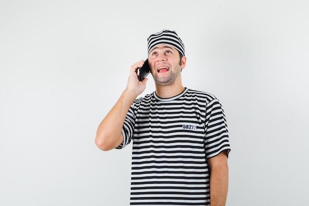 Jovem macho falando no celular em t-shirt, chapéu e olhando alegre, vista frontal.
