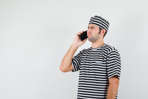 Jovem macho falando no celular em t-shirt, chapéu e olhando triste, vista frontal.