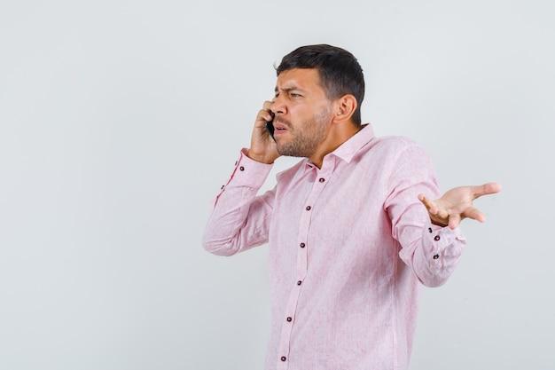 Jovem macho falando no celular em uma camisa rosa e parecendo nervoso, vista frontal.
