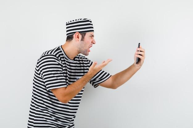 Jovem macho falando no chat de vídeo em t-shirt, chapéu e olhar zangado. .