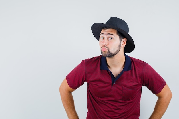 Jovem macho fazendo beicinho os lábios em t-shirt, chapéu e parecendo estranho, vista frontal.