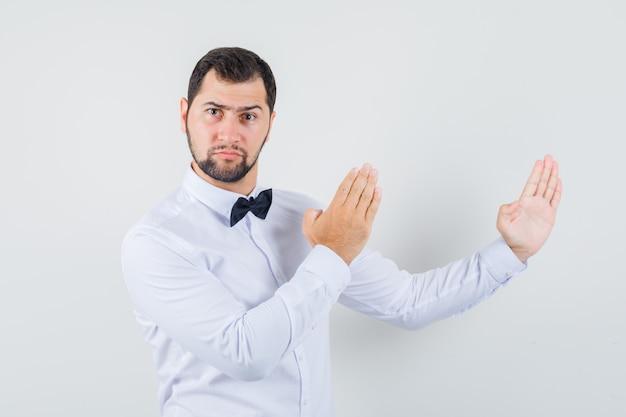 Jovem macho fazendo gesto de kung fu em camisa branca e parecendo com raiva. vista frontal.