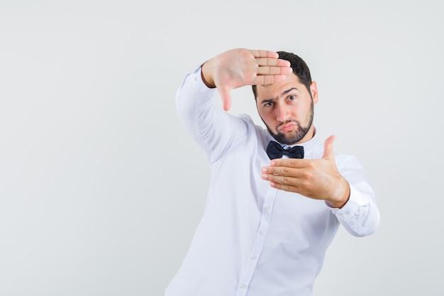 Jovem macho fazendo gesto de quadro em camisa branca e olhando focado, vista frontal.
