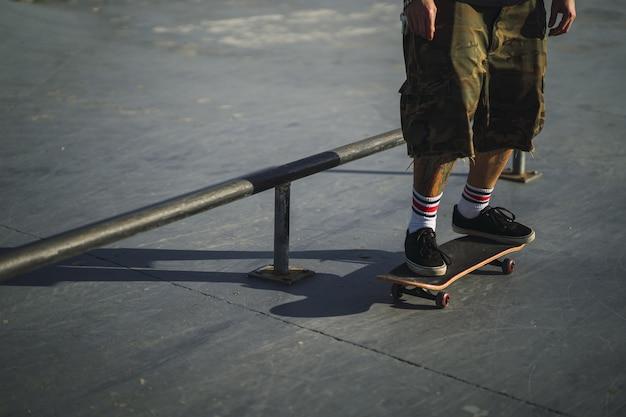 Jovem macho fazendo manobras diferentes com um skate no parque