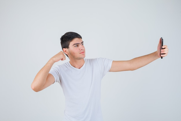 Jovem macho fazendo selfie enquanto mostra os músculos dos braços em uma camiseta e parece alegre. vista frontal.