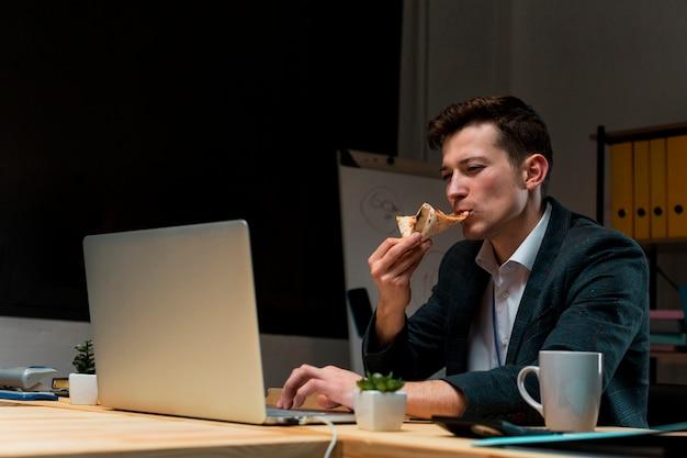 Jovem macho fazendo um lanche enquanto trabalhava em casa