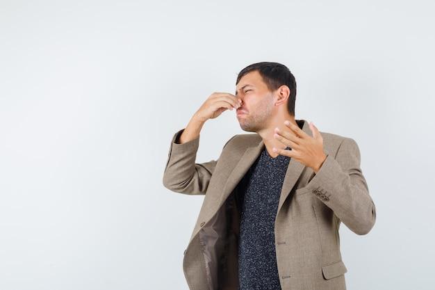 Jovem macho fechando o nariz na jaqueta marrom acinzentada, camisa preta e parecendo nojento, vista frontal.
