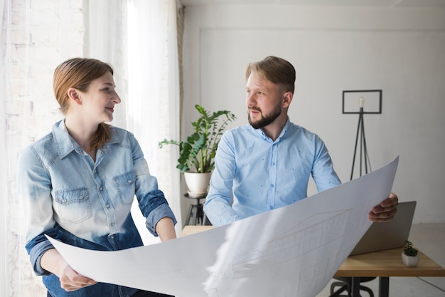 Jovem, macho fêmea, coworker, olhando um ao outro, enquanto, segurando, blueprint, em, escritório