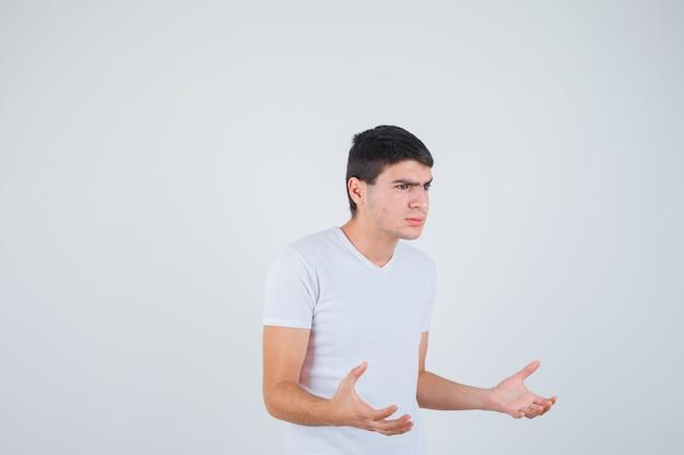 Jovem macho fingindo pegar algo na camiseta e parecendo sério. vista frontal.
