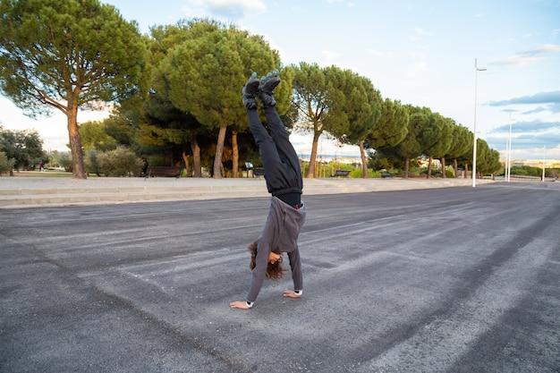 Jovem macho flexível bonito no sportswear com patins fazendo parada de mãos na estrada no parque bonito da cidade