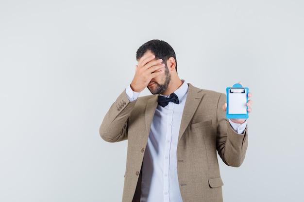 Jovem macho mostrando a mini prancheta com a mão no rosto no terno e parecendo envergonhado. vista frontal.