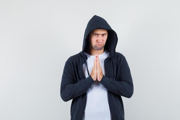 Jovem macho mostrando gesto namastê em camiseta, jaqueta e olhar triste. vista frontal.