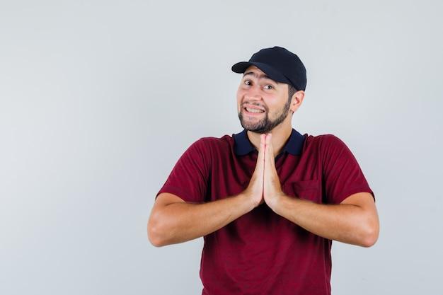 Jovem macho mostrando gesto namastê em camiseta vermelha, boné preto e parecendo satisfeito. vista frontal.