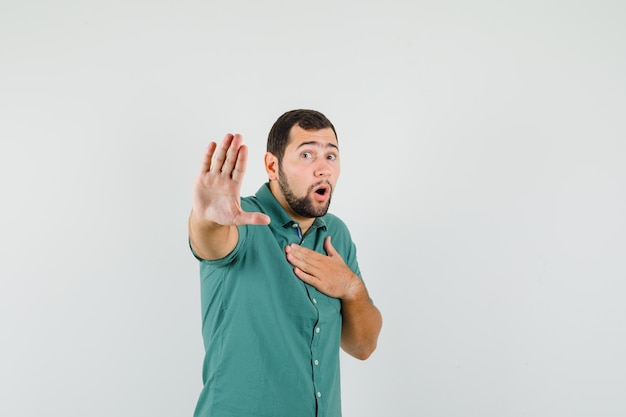 Jovem macho mostrando o gesto de parada na camisa verde e olhando animado, vista frontal.