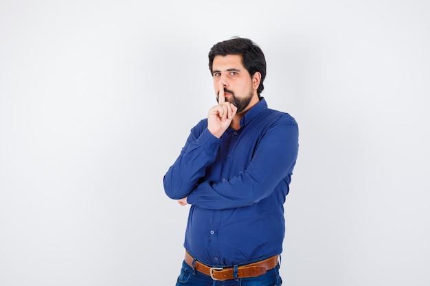 Jovem macho mostrando o gesto de silêncio na camisa, jeans e parecendo em paz. vista frontal.