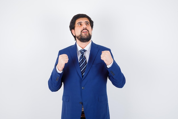 Jovem macho mostrando o gesto vencedor na camisa, jaqueta, gravata, vista frontal.