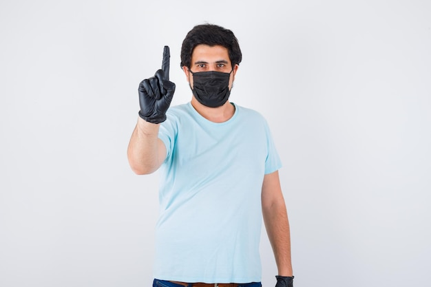 Jovem macho mostrando o número um em t-shirt e parecendo confiante. vista frontal.