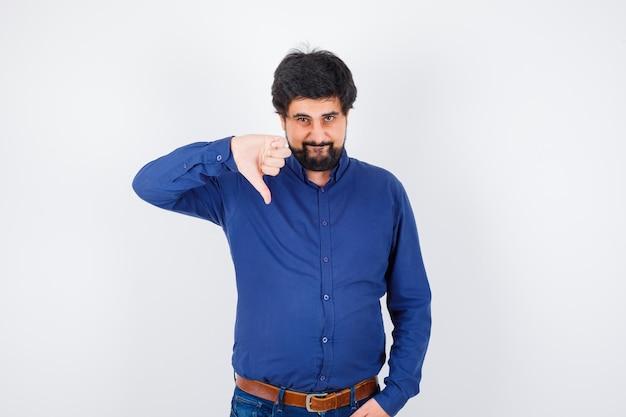 Jovem macho mostrando o polegar para baixo em uma camisa, jeans e parecendo confiante. vista frontal.