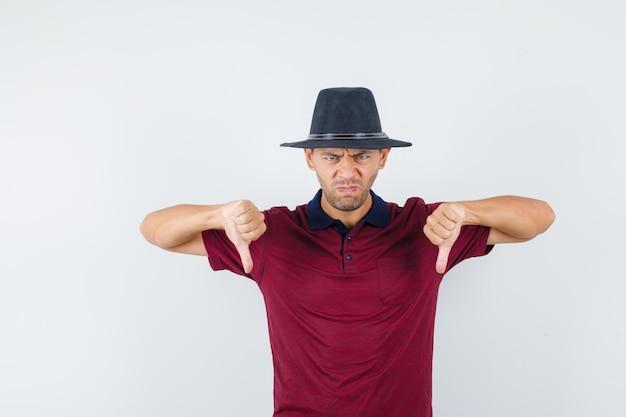 Jovem macho mostrando o polegar para baixo na camisa vermelha, chapéu preto e olhando com raiva, vista frontal.