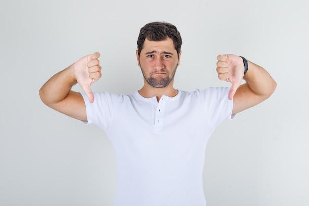 Jovem macho mostrando os polegares para baixo em uma camiseta branca e parecendo triste